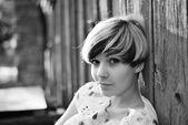 красивая девушка с современной прической, позирует возле забора — Стоковое фото