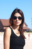 Girl in black gown and sunglasses on beach — Stock Photo
