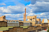 Large factory with smoking chimneys against the blue sky — Stock Photo