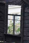 Burned wooden window frame — Stock Photo