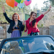Two young happy girls with air balloons in cabrio — Stock Photo
