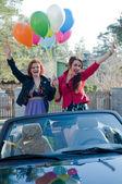 Две молодые девушки счастливы с воздушных шаров в cabrio — Стоковое фото