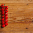 Stock Photo: The branch of cherry tomatoes on a decorative board.