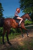 Femme aux cheveux rouges, assis sur un cheval — Photo