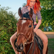 Woman with red hair sitting on a horse — Stock Photo