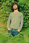 Portrait of handsome man on tree — Stock Photo