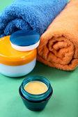 Natürmort kozmetik krem ve yeşil bir havlu — Stok fotoğraf