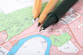 Topographic map with pencils and a RollerBall — Stock Photo