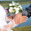 Hands and rings with wedding bouquet - Stock Photo