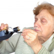 Grandmother pours a medicine in spoon isolated on white — Stock Photo #11419641