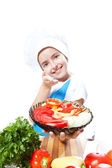 Little chef cook with a plate of salad and vegetables — Stock Photo