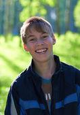 Niño sonriente sobre un fondo verde — Foto de Stock