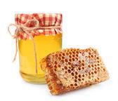 Jar of honey and honey honeycombs — Stock Photo
