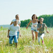 Friends running in meadow — Stock Photo