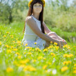 Girl sitting in dandelion meadow — Stock Photo