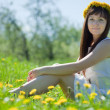Girl sitting in dandelion wreath — Stock Photo #11498326