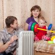 Family at home near oil heater — Stock Photo #11498370