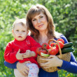 Stock Photo: Womand baby with vegetables in garden