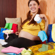 Pregnant woman with baby's clothes — Stock Photo