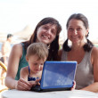 Family  with laptop  at resort  beach — Stock Photo