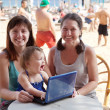 Women and  girl   with laptop   at  beach — Stock Photo