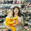 Happy mother with child chooses baby shoes — Stockfoto