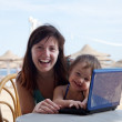 Royalty-Free Stock Photo: Happy family   with laptop at  beach