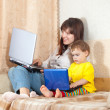 Foto Stock: Happy mother and child with laptops