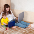 Happy woman with toddler using laptops — Stock Photo