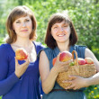 Happy  women with apples in orchard — Stock Photo