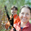 Stock Photo: Female gardener cuts branches