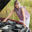 Woman looking under car hood — Stock Photo #11498813