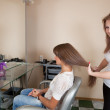 Hair stylist working with long-haired girl - Stok fotoğraf