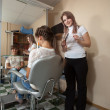 Stock Photo: Hair stylist working with long-haired girl
