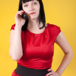 Woman in red speak by phone over yellow — Stock Photo #11499342