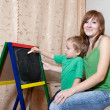 Stock Photo: Mother and child draws on blackboard