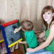 Foto Stock: Woman and children draws on blackboard