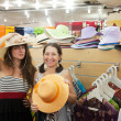Women chooses hat at shop — Stock Photo #11499464
