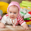 Royalty-Free Stock Photo: Baby girl with heap of baby&#039;s wear
