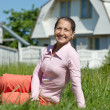 Happy mature woman against residence — Stock Photo #11499649