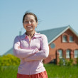 Happy mature woman against her home — Stock Photo #11499650