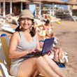 Stock Photo: Happy womsitting with laptop at beach