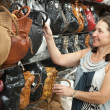 Mature womchooses leather bag — Stockfoto #11499682