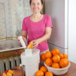 Stock Photo: Mature woman making orange juice