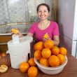 Mature woman making orange juice — Stock Photo