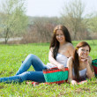 Happy women relaxing in grass — Stock Photo