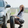 Woman during wheel changing a — Stock Photo
