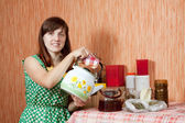 Woman brews herbs in teapot — Stock Photo