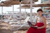Woman using laptop at resort beach — Stock Photo