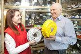 Man buys brake wheel in auto parts store — Stock Photo